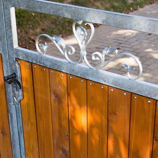 Einfahrtstor mit Metallverzierung und Holzfüllung